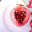 Pomegranate seeds in the form of heart on a wooden background. — Stock Photo #61457769