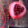 Pomegranate seeds in the form of heart on a wooden background. — Fotografia Stock  #61457795