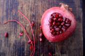 Pomegranate seeds in the form of heart on a wooden background. — Stock Photo