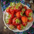 Strawberry on white plate  wooden table — Stock Photo #63744335