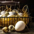 Basket of freshly laid  eggs lying on straw in the barn — Stock Photo #64301009