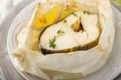 Cod fillets  baked in parchment paper with slices of lemon — Stock Photo