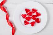 Heart shaped red jelly candies on white dish with ribbon on vint — Stock Photo