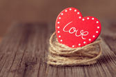 Red valentine's day heart with text in nest on wooden background — Stock Photo
