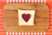 Slice of wholewheat toast with red berry jam in the shape of hea — Stock Photo