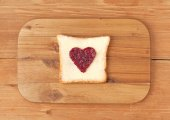 Slice of wholewheat toast with berry jam in the shape of heart o — Stock Photo