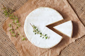Sliced round camembert cheese traditional milk creamy dairy product with thyme on vintage parchment — Stock Photo