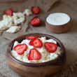 Homemade cottage cheese natural organic breakfast with strawberry and sour cream in wooden dish on rustic kitchen table — Stock Photo #76037579