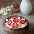 Cottage cheese healthy organic nutrition breakfast with milk and strawberry in rustic wooden dish on vintage kitchen table background — Stock Photo #76037619