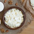 Cottage cheese healthy protein breakfast with sour cream and almond nuts in rustic wooden dish on vintage kitchen table background — Stock Photo #76037635