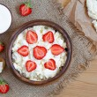 Healthy homemade cottage cheese breakfast or lunch with strawberry, sour cream and nuts in wooden dish on rustic kitchen table background — Stock Photo #76037665
