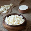 Traditional homemade cottage cheese with sour cream in rustic wooden dish on vintage kitchen table background — Stock Photo #76037763