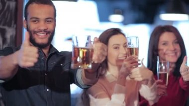 Young company showing thumb up and  lifts up a glass of beer — Stock Video