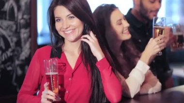 Smiling young beautiful girl with a beer in the company of friends — Stock Video