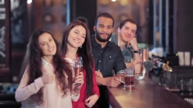 A group of friends at the bar with a beer smiling and showing thumb up — Stock Video