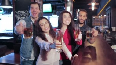 Four old friends at the bar with a glass of beer is welcomed new friends — Stock Video