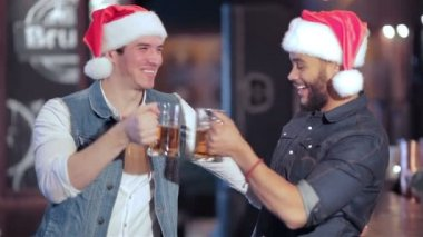 Two jolly Santa boys with glasses of beer — Stock Video