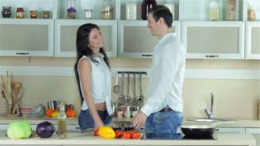 Young beautiful couple meet in the kitchen, kissing and drinking grape juice — Stock Video