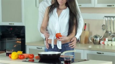 Beautiful girl doing cutting tomatoes, guy holding her by the waist — Stock Video