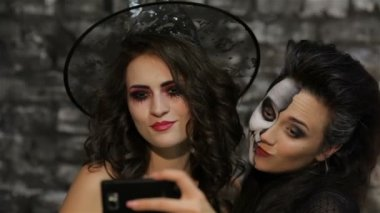 Girls-witch and skeleton make selfie — Stock Video