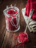 Jar and spoon with saffron — Stock Photo