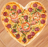 Meat pizza with ham, salami, tomatoes and cheese topped with fresh Italian herbs in heart shape for valentine — Stock Photo