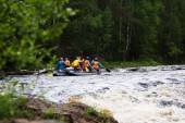 Group of athletes floats on an inflatable catamaran on the mountain river — Stock Photo