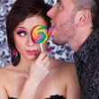 Beautiful girl with a lollipop in his hand a man who licks — Stock Photo #53553059
