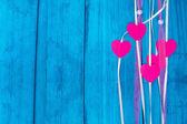 Mavi ahşap arka plan üzerinde renkli bir ip üzerinde kırmızı Kalpler — Stok fotoğraf