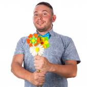 Attractive adult man with stubble in a bow tie in summer shirt holding a bouquet of flowers on isolated white background — Stock Photo