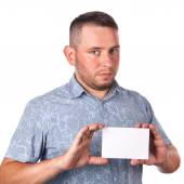 Attractive adult man with stubble in summer shirt in his hands holding a white sheet with space for advertising text on an isolated white background — Stock Photo