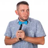 Serious adult man with a beard in a blue bow tie in summer shirt with a firearm in the hands of the hands on an isolated white background — Stock Photo
