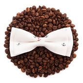 Bow tie patterned sea anchor lie on the circle of coffee beans isolated on white background — Stock Photo