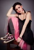 Beautiful girl in black and pink dress and sneakers sitting on a chair cross-legged on a gray background — Stock Photo