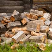 Chaotic pile of firewood logs lying on green grass — Stock Photo