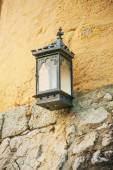 Street lamp with a candle attached to the outside of the house — Stock Photo