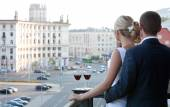 Couple on balcony with a glass of wine watching the city. — Stock Photo