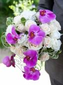 Wedding bouquet. Bouquet of fresh flowers for the wedding ceremony. Bouquet of orchids, roses and other flowers in the groom's hands closeup. — Stock fotografie