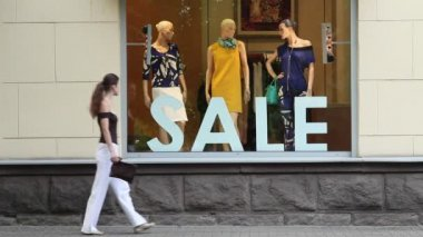 Sale. Woman passing by shop window and looking at mannequins. — Vídeo de stock
