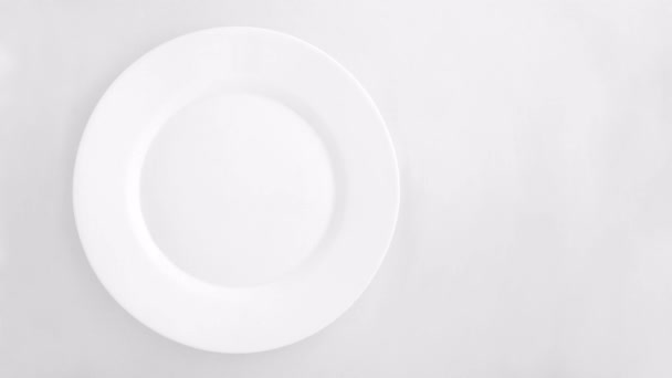 Vintage cutlery set with fork, knife, spoon and plate appear on a white background. — Vidéo