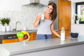 Smiling young woman with glass of milk — Stock Photo