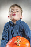 Little boy holding with difficulty a big pumpkin. Halloween them — Stock Photo