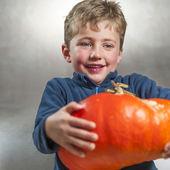 Little boy holding a big orange pumpkin. Halloween theme — Stock Photo