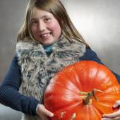 Closeup portrait of little girl posing with a big pumpkin — Stock Photo