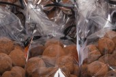 Closeup on chocolate truffles in plastic bags stacked — Stock Photo