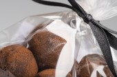 Closeup on chocolate truffles in luxury plastic bag with ribbon — Stock Photo
