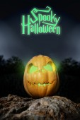 Spooky Halloween neon pumpkin in on a rock in the darkness — Stock Photo