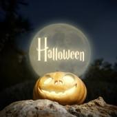 Halloween lighting pumpkin in moon light on a rock — Stock Photo
