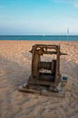 Old boat winch on the beach — Stock Photo