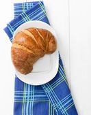 Croissant over bluish cloth — Stock Photo